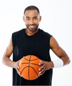 Portrait éducateur sportif tenant un ballon de basket dans ses mains